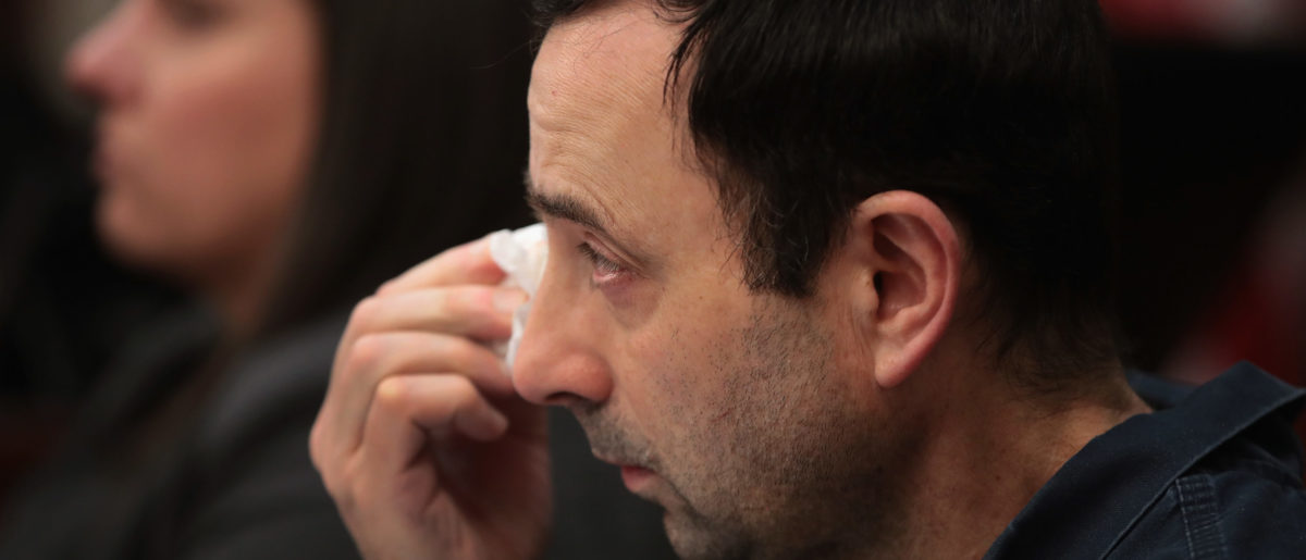 LANSING, MI - JANUARY 17: Larry Nassar wipes a tear as he listens to Carrie Hogan deliver a victim impact statement at his sentencing hearing on January 17, 2018 in Lansing, Michigan. Nassar has pleaded guilty in Ingham County, Michigan, to sexually assaulting seven girls, but the judge is allowing 101 ofl his accusers to speak. Nassar is currently serving a 60-year sentence in federal prison for possession of child pornography. (Photo by Scott Olson/Getty Images)