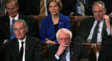 Elizabeth Warren and Bernie Sanders stare blankly while Trump addresses the audience. (Photo by Alex Wong/Getty Images)