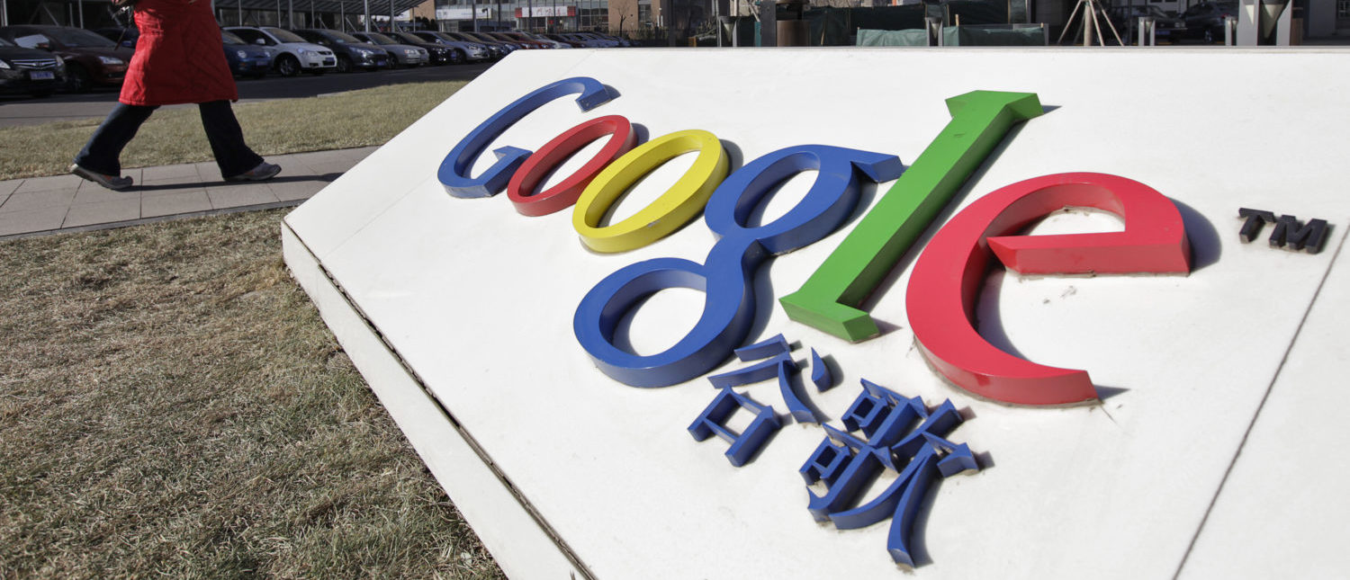 A woman walks past the logo of Google in front of its headquarters in Beijing January 12, 2011. Google is reloading its guns in China to focus on display advertisements and the booming export sector a year after a blowout with Beijing over censorship and hacking all but ensured its demise in the country. Picture taken on January 12, 2011. To match Analysis GOOGLE-CHINA/ This logo has been updated and is no longer in use. REUTERS/Christina Hu