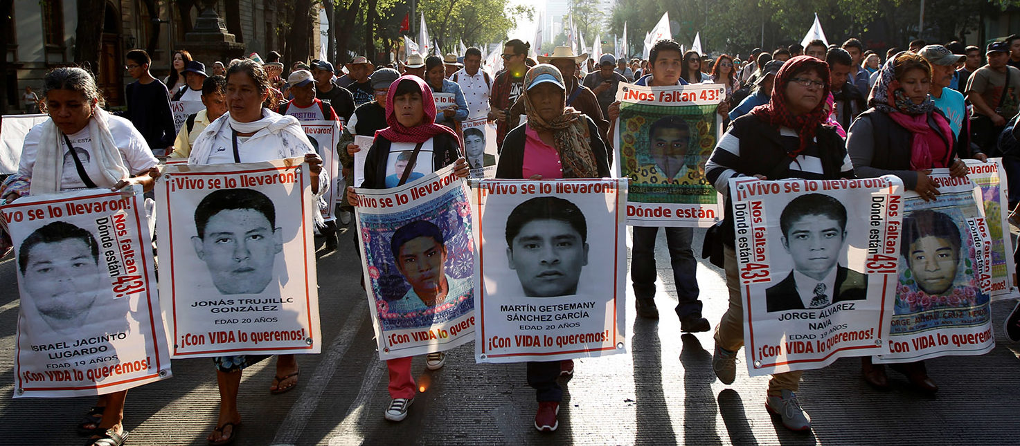 Relatives hold up signs with images of some of the 43 missing students of Ayotzinapa College Raul Isidro Burgos as they take part in a march to mark the 29th month anniversary of the disappearance of the students in the state of Guerrero in Mexico City, Mexico February 26, 2017.  REUTERS/Carlos Jasso