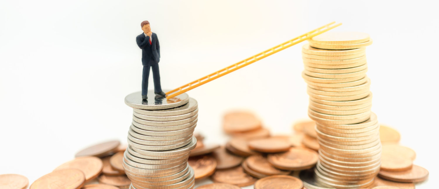 A businessman standing on top of coins, looking into how he can improve his earnings. [Shutterstock -Fahkamram]