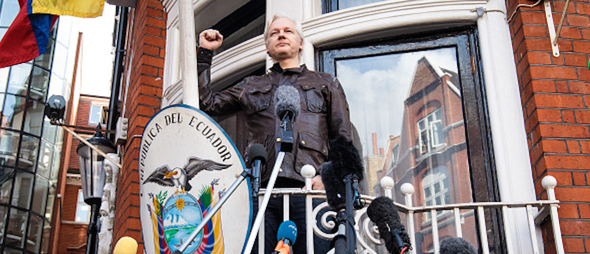 LONDON, ENGLAND - MAY 19: Julian Assange puts his fist in the air as he steps out to speak to the media from the balcony of the Embassy Of Ecuador on May 19, 2017 in London, England. Julian Assange, founder of the Wikileaks website that published US Government secrets, has been wanted in Sweden on charges of rape since 2012. He sought asylum in the Ecuadorian Embassy in London and today police have said he will still face arrest if he leaves. (Photo by Jack Taylor/Getty Images)