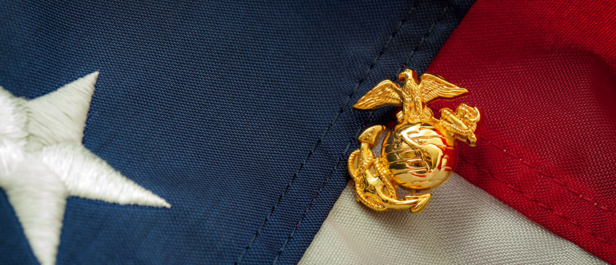 Marine Corps Pin Over American Flag Shutterstock