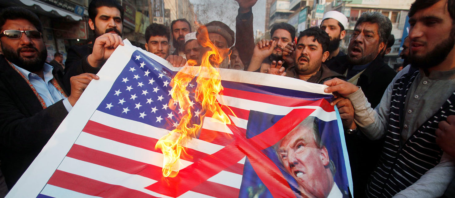 People burn a sign depicting a U.S. flag and a picture of U.S. President Donald Trump as they take part in an anti-U.S. rally in Peshawar, Pakistan, January 5, 2018. REUTERS/Fayaz Aziz