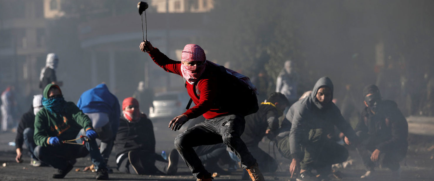 "A Palestinian protester uses a sling to hurl stones towards Israeli troops during clashes as Palestinians call for a ""day of rage"" in response to U.S. President Donald Trump's recognition of Jerusalem as Israel's capital, near the Jewish settlement of Beit El, near the West Bank city of Ramallah December 8, 2017. REUTERS/Mohamad Torokman"