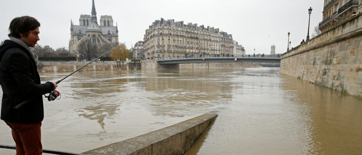 A man fishes on the flooded banks of the River Seine in Paris, France, after days of almost non-stop rain caused flooding in the country, January 27, 2018. REUTERS/Pascal Rossignol