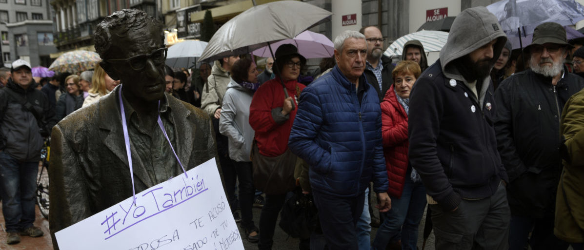 "People walk past Woody Allen sculpture during the rally on the World Day for the Elimination of Violence against Women in Oviedo, northern Spain, November 25, 2017. The banner reads""Your wife accused you of abusing your daughter. Nobody believed her. Liar, selfish, revengeful, they shouted at her. Nobody believed them. And nobody helped them."" REUTERS/Eloy Alonso"