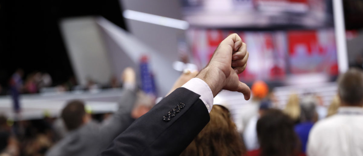 A Republican National Convention delegate gives a thumbs down as the Chair announces that the convention will not hold a roll-call vote on the Republican National Convention Rules Committee's report and rules changes and rejects the efforts of anti-Trump forces to hold such a vote, at the Republican National Convention in Cleveland, Ohio, U.S. July 18, 2016. REUTERS/Mark Kauzlarich  - HT1EC7I1MWWAQ