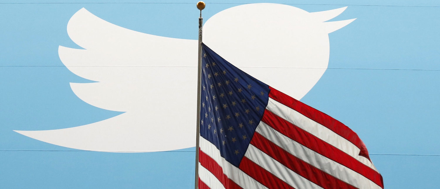 The Twitter Inc. logo is shown with the U.S. flag during the company's IPO on the floor of the New York Stock Exchange in New York, November 7, 2013.    REUTERS/Lucas Jackson/File Photo - HT1ECCF1T7B10