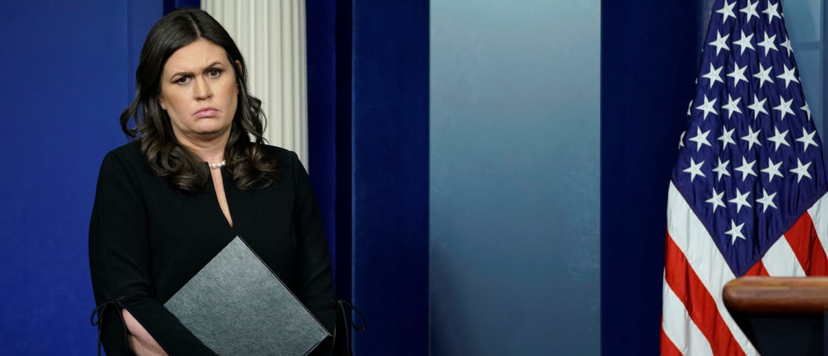 White House Press Secretary Sarah Sanders waits to take her place at the lectern for a press briefing at the White House in Washington, U.S., December 12, 2017.  REUTERS/Kevin Lamarque - RC1BEC3A1800