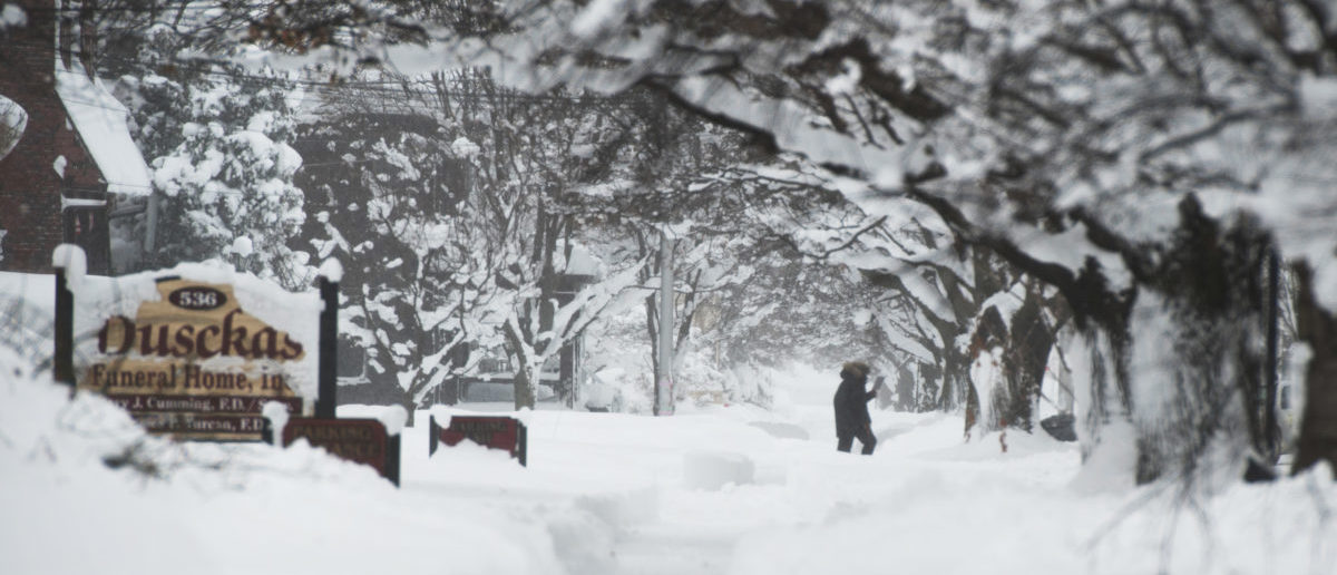 A resident is out walking on 10th street after two days of record-breaking snowfall in Erie