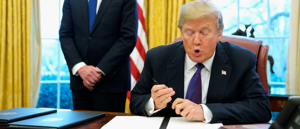 U.S. President Donald Trump, flanked by U.S. Trade Representative Robert Lighthizer, reads a directive to impose tariffs on imported washing machines before signing it in the Oval Office at the White House in Washington, U.S. January 23, 2018.  REUTERS/Jonathan Ernst - RC1F6B9D9700