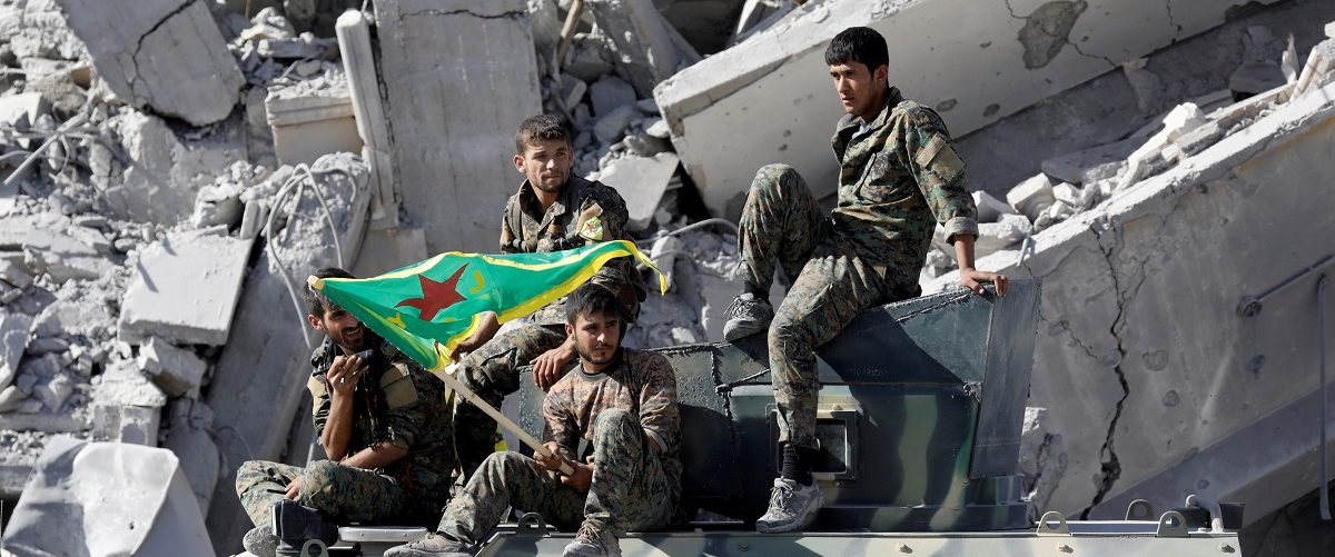 Fighters of Syrian Democratic Forces ride atop an armoured vehicle after Raqqa was liberated from the Islamic State militants, in Raqqa, Syria October 17, 2017. REUTERS/Erik De Castro.