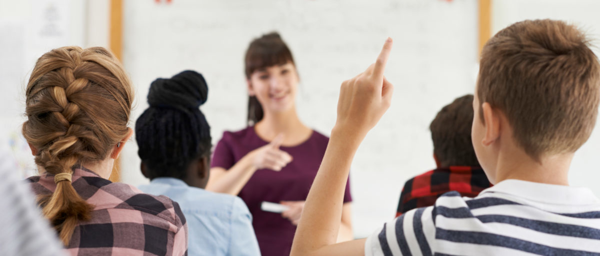 Male student answers a question in a classroom. (Shutterstock/SpeedKingz)