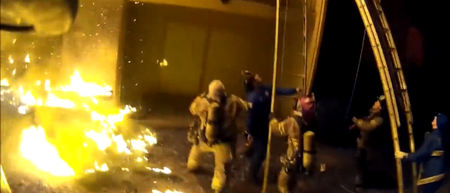 Screenshot from CBS News video of firefighters catching children lobbed from burning building