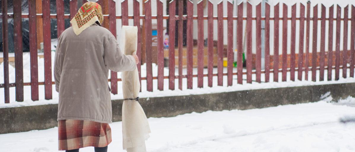 grandma walking in snow in winter holidays, grandma walks in folk costume Shutterstock/ Pelle Zoltan