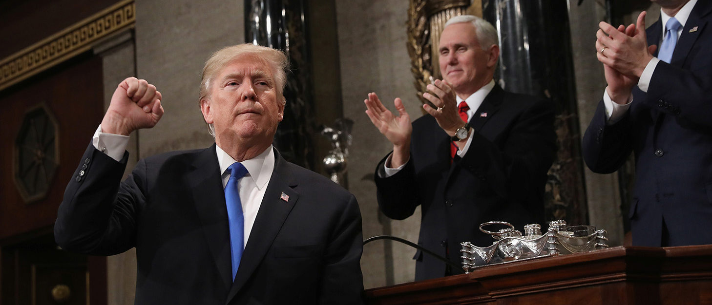U.S. President Donald J. Trump (L) gestures at the podium in front of U.S. Vice President Mike Pence (L) and Speaker of the House U.S. Rep. Paul Ryan (R-WI) during his first State of the Union address to a joint session of Congress inside the House Chamber on Capitol Hill in Washington, U.S., January 30, 2018. REUTERS/Win McNamee/Pool