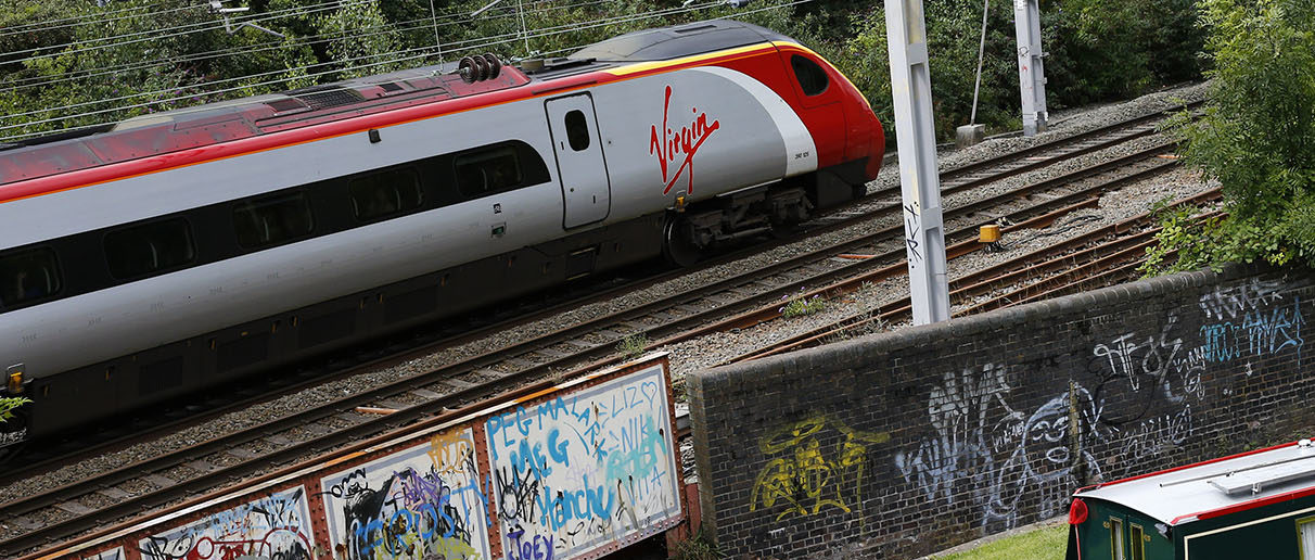 A Virgin train passes a canal in Stoke-on-Trent, central England August 19, 2014. Regulated rail fares will rise in January 2015 by 3.5%.  REUTERS/Darren Staples