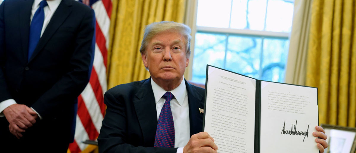 FILE PHOTO: U.S. President Donald Trump, flanked by U.S. Trade Representative Robert Lighthizer, holds up a directive to impose tariffs on imported washing machines after signing it in the Oval Office at the White House in Washington, U.S. January 23, 2018.  REUTERS/Jonathan Ernst