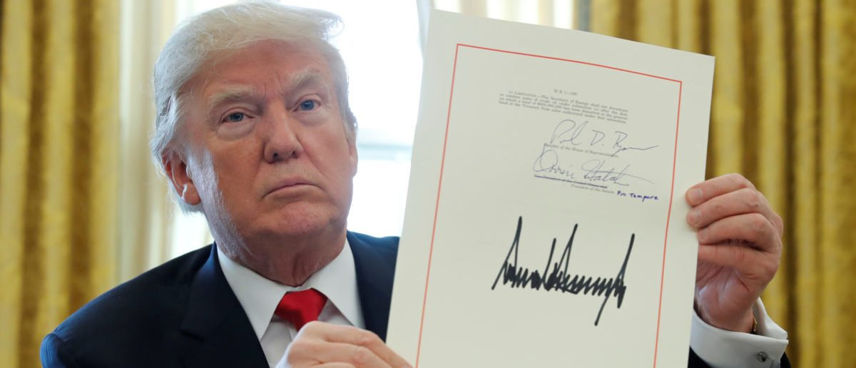 FILE PHOTO: U.S. President Donald Trump displays his signature after signing the $1.5 trillion tax overhaul plan in the Oval Office of the White House in Washington, U.S., December 22, 2017. REUTERS/Jonathan Ernst