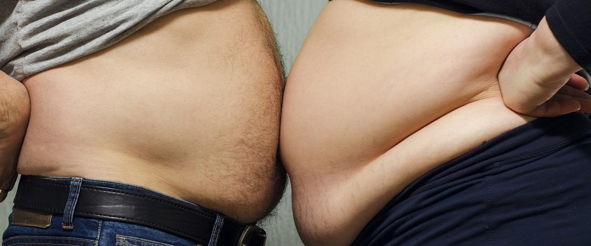 Two fat people with their bellies touching. Phoenixns/Shutterstock.
