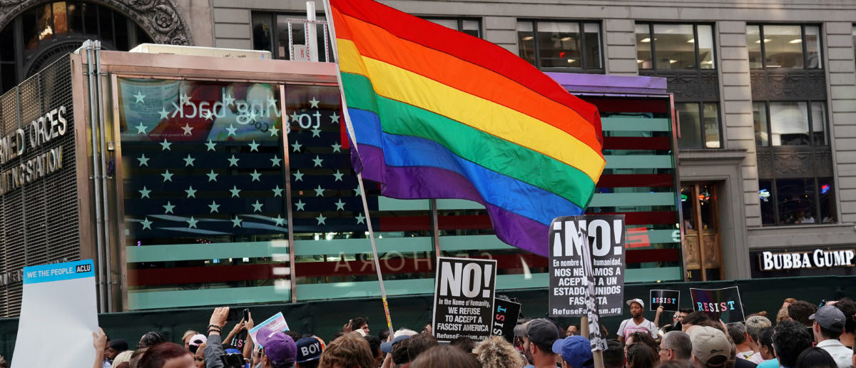 FILE PHOTO: A rainbow flag flies as people protest U.S. President Donald Trump's announcement that he plans to reinstate a ban on transgender individuals from serving in any capacity in the U.S. military, in Times Square, in New York City, New York, U.S., July 26, 2017. REUTERS/Carlo Allegri/File Photo