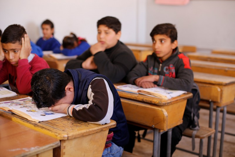Hussein al-Khalaf, 13, reacts as he sits in a classroom at a school in Sahnaya, near Damascus Syria February 1, 2018. Picture taken February 1, 2018. REUTERS/Omar Sanadiki