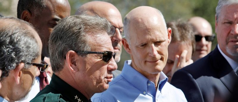 Broward County Sheriff Scott Israel speaks to the media while Florida Governor Rick Scott listens outside Marjory Stoneman Douglas High School one day after a shooting at the school left 17 dead, in Parkland, Florida, U.S., February 15, 2018. REUTERS/Jonathan Drake