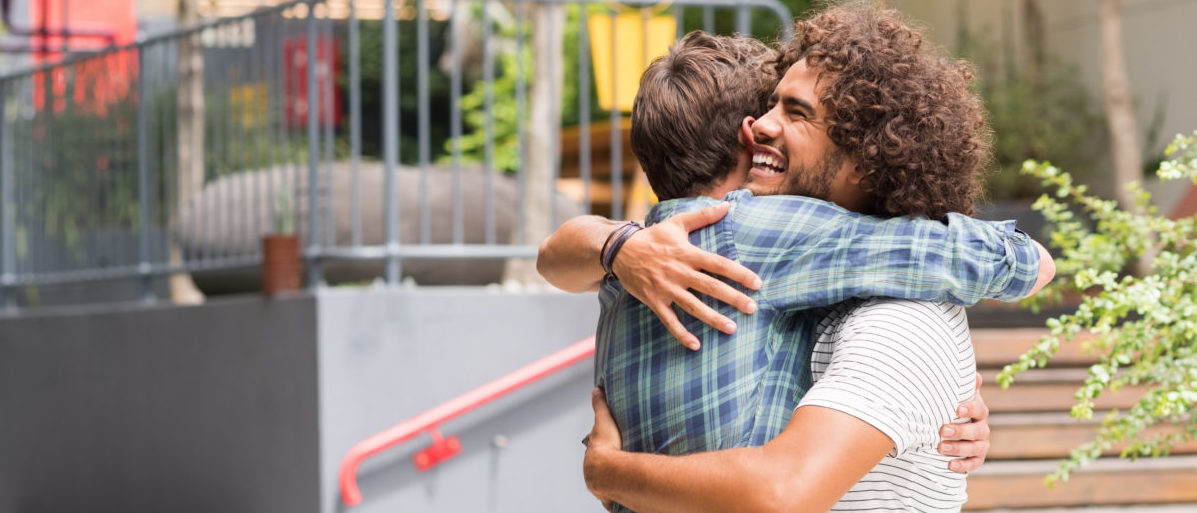 Cheerful best friends embracing each other outside coffee shop. Two young multiethnic guys hugging each other. Happy smiling best friends meeting each other after a long time with a hug. Shutterstock/ Rido