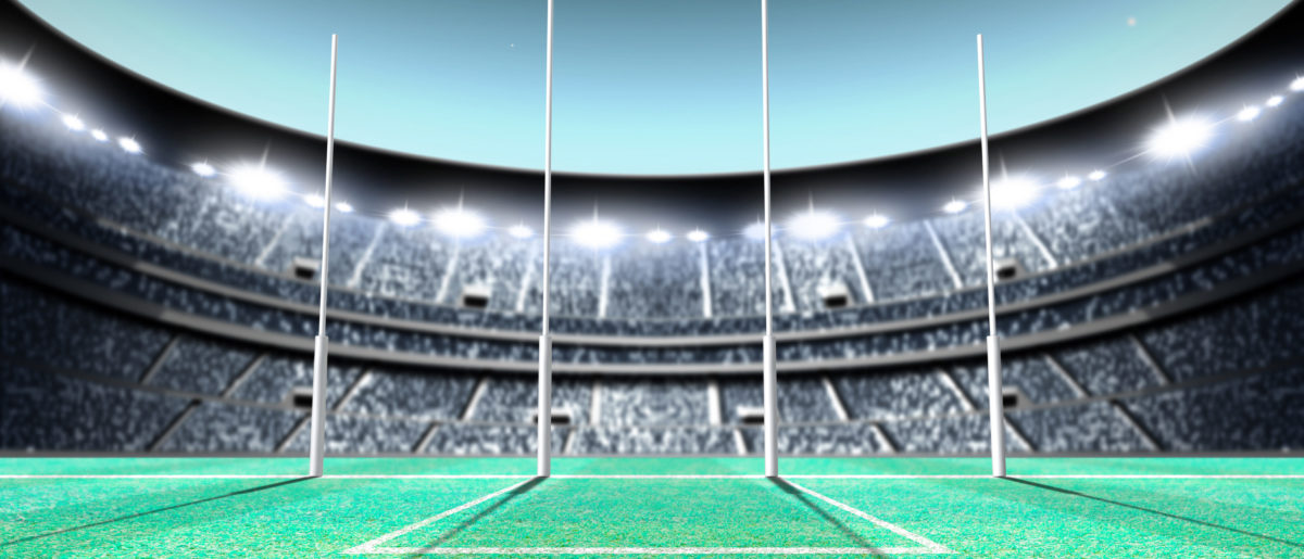 A generic seated aussie rules stadium showing goal posts on a green grass pitch. (Shutterstock/Inked Pixels)