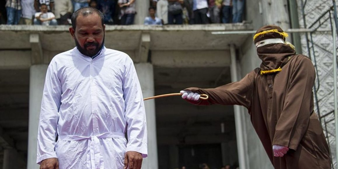 An Indonesian Sharia police whips a man during a public caning ceremony outside a mosque in Banda Aceh, capital of Aceh province on September 18, 2015. Three women and 14 men arrested for sexual offenses and gambling were caned in front of the mosque in full view of the public following the Friday prayer. Aceh is the only province of Indonesia that is enforcing the Islamic Sharia law and violators are punished by public caning. (CHAIDEER MAHYUDDIN/AFP/Getty Images)