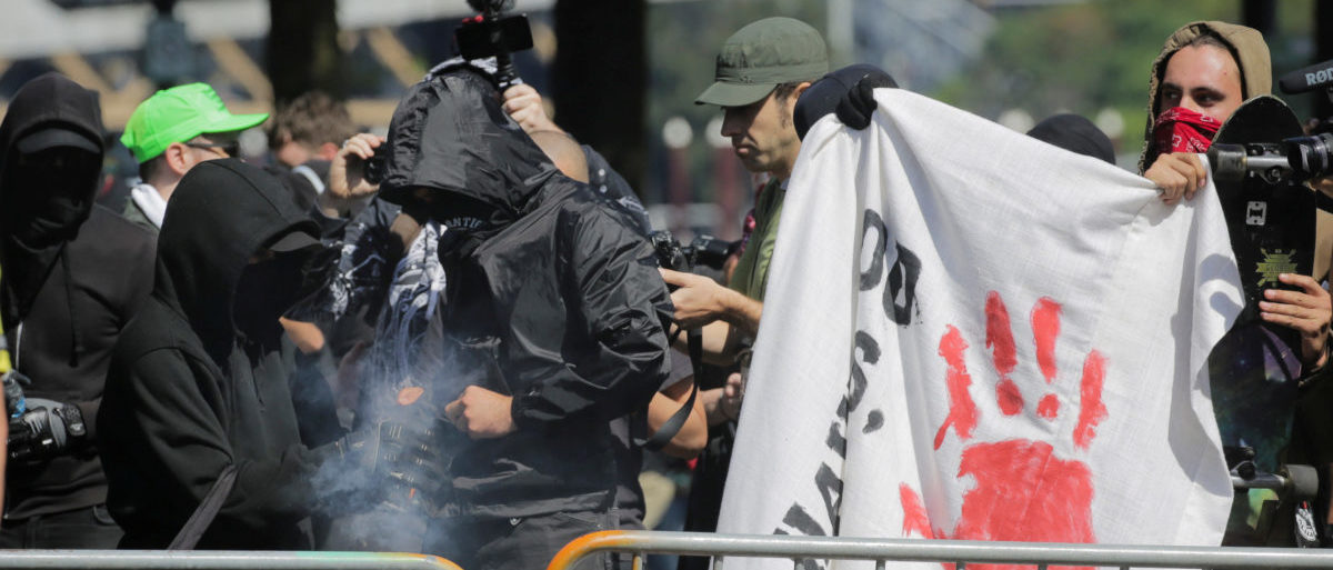 Antifa counter protesters against right-wing group Patriot Prayer light a smoke grenade in Portland, Oregon, U.S. Sept. 10, 2017. Patriot Prayer announced they were moving their Sunday rally from downtown Portland to nearby Vancouver, Washington, citing fears for their safety. REUTERS/Elijah Nouvelage - RC19C2DF8B70