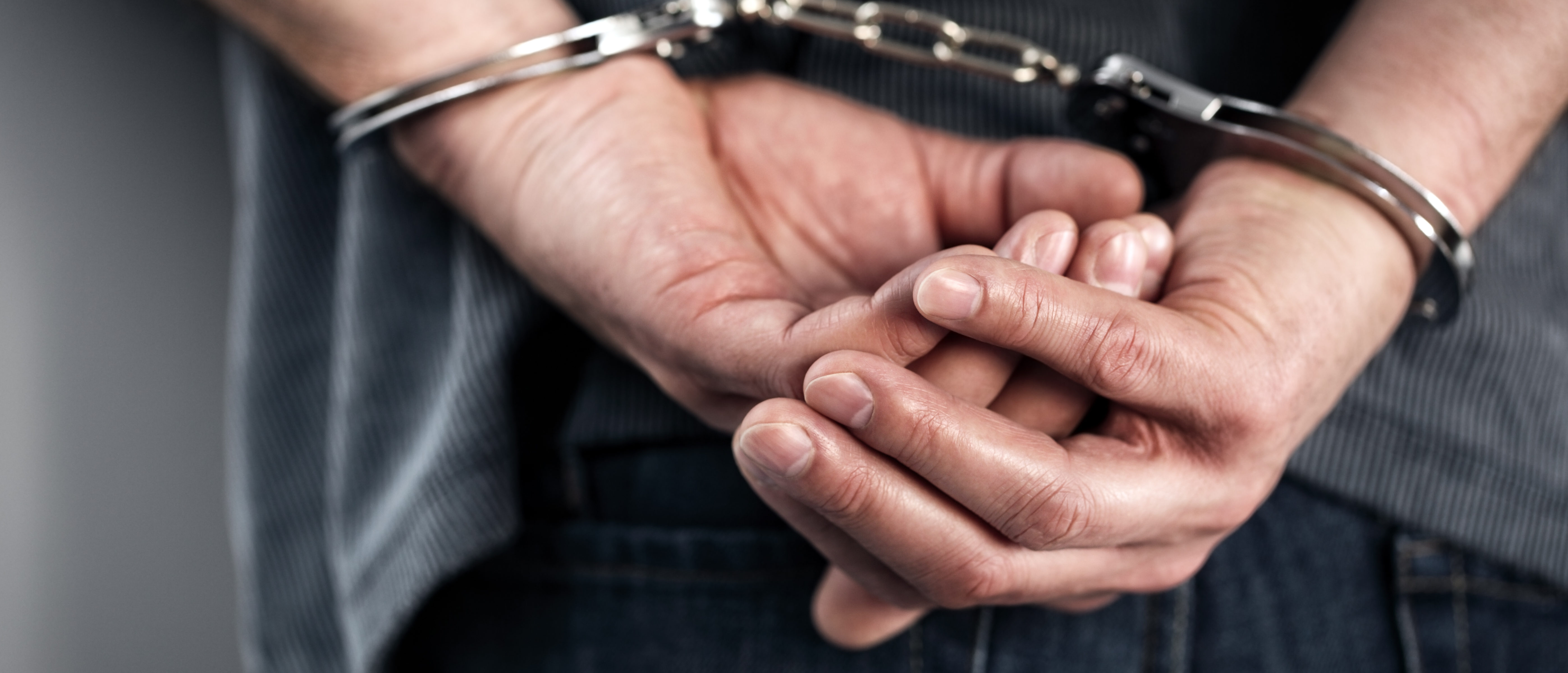 Arrested man in handcuffs with hands behind back. (Shutterstock/Brian A Jackson)