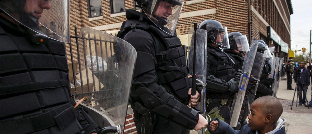 A young boy greets police officers in riot gear during a march in Baltimore, Maryland May 1, 2015 following the decision to charge six Baltimore police officers -- including one with murder -- in the death of Freddie Gray, a black man who was arrested and suffered a fatal neck injury while riding in a moving police van, the city's chief prosecutor said on Friday. REUTERS/Lucas Jackson