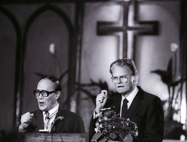 As American evangelist Billy Graham preaches to the congregation at Chongwenmen church Sunday, April 17, 1988, his words and gestures along with their fervor are translated into Chinese by Philip Teng. It was Graham's first visit to China.  REUTERS/Edward Nachtrieb