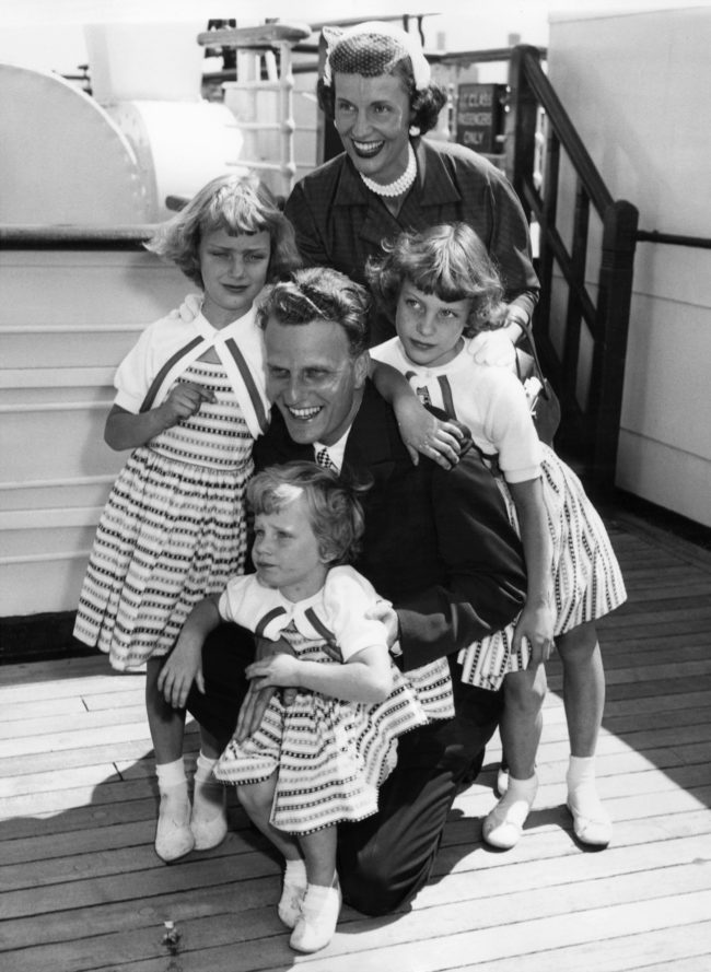 "Billy Graham, 35, the American evangelist, is greeted by his wife and children, Virginia, 8 (L), Anne, 6 (R) and Ruth (Bunny), 3 (foreground) aboard the liner ""Queen Mary"" on his return to New York June 7, 1954, from a religious tour of Europe. (Photo: AFP/AFP/Getty Images)"