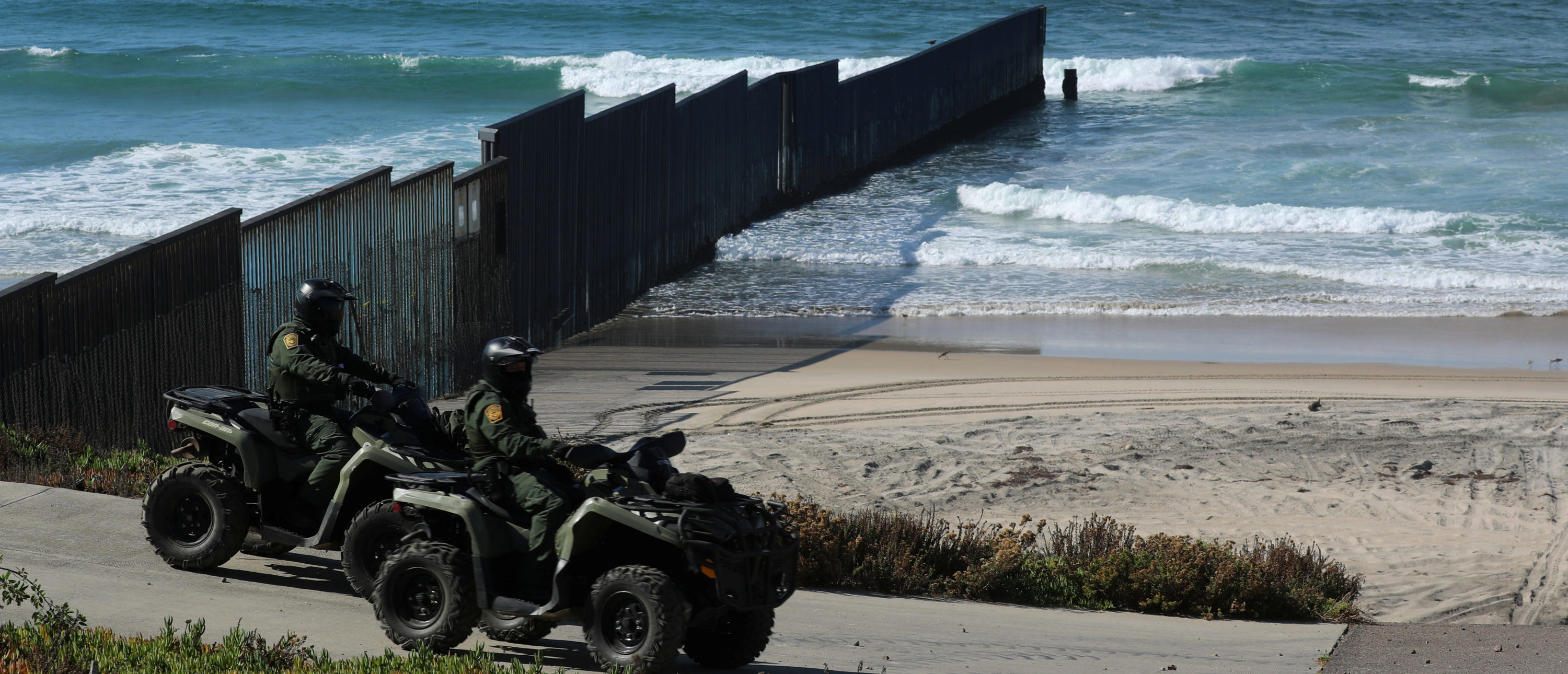 U.S. Customs and Border patrol agents on all-terrain vehicles look over over the Mexico-U.S. border wall where it enters the Pacific Ocean at Border Field State Park in San Diego, California, November 18, 2017. REUTERS/Mike Blake