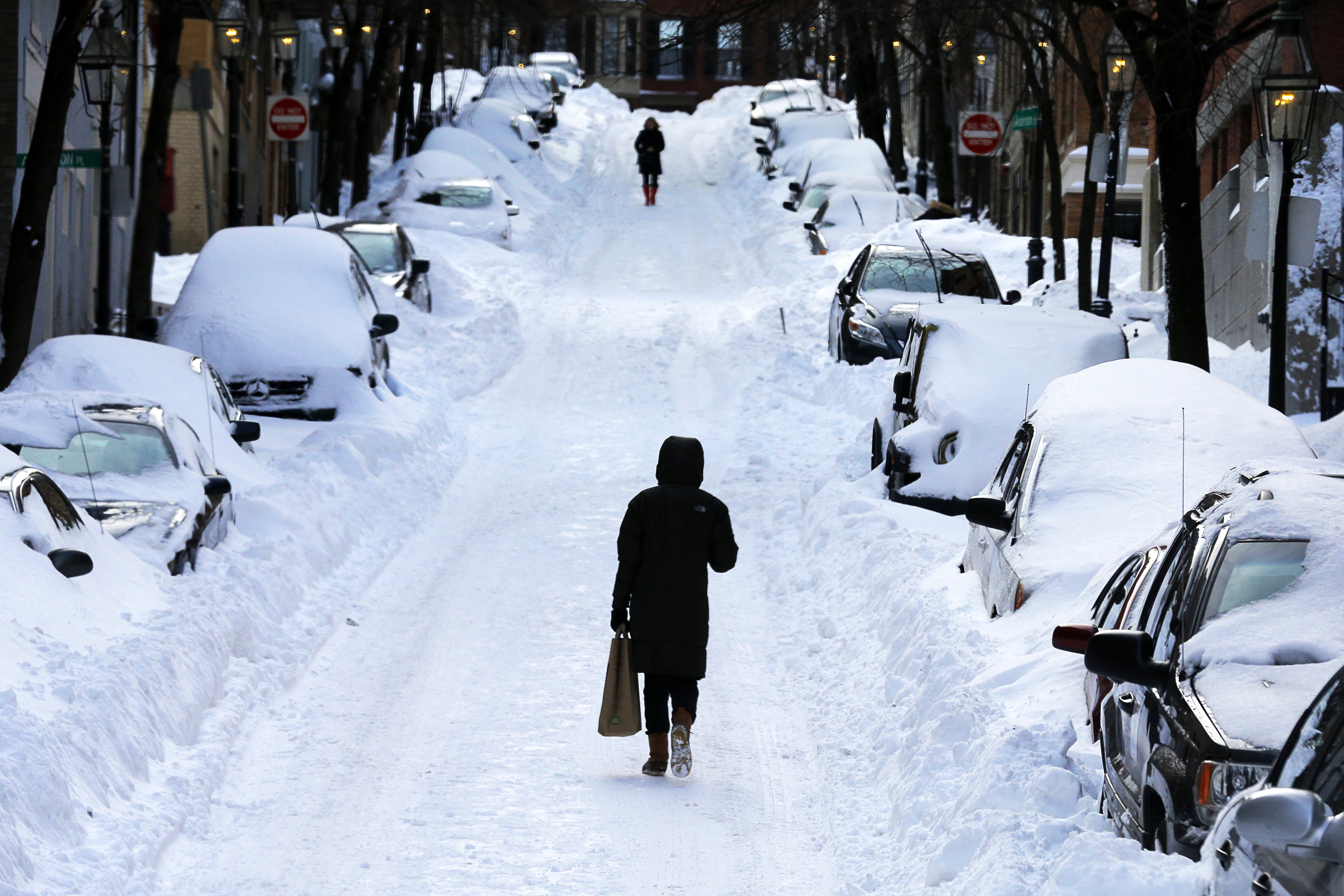A pedestrian walks in the middle of the street following a winter blizzard in Boston