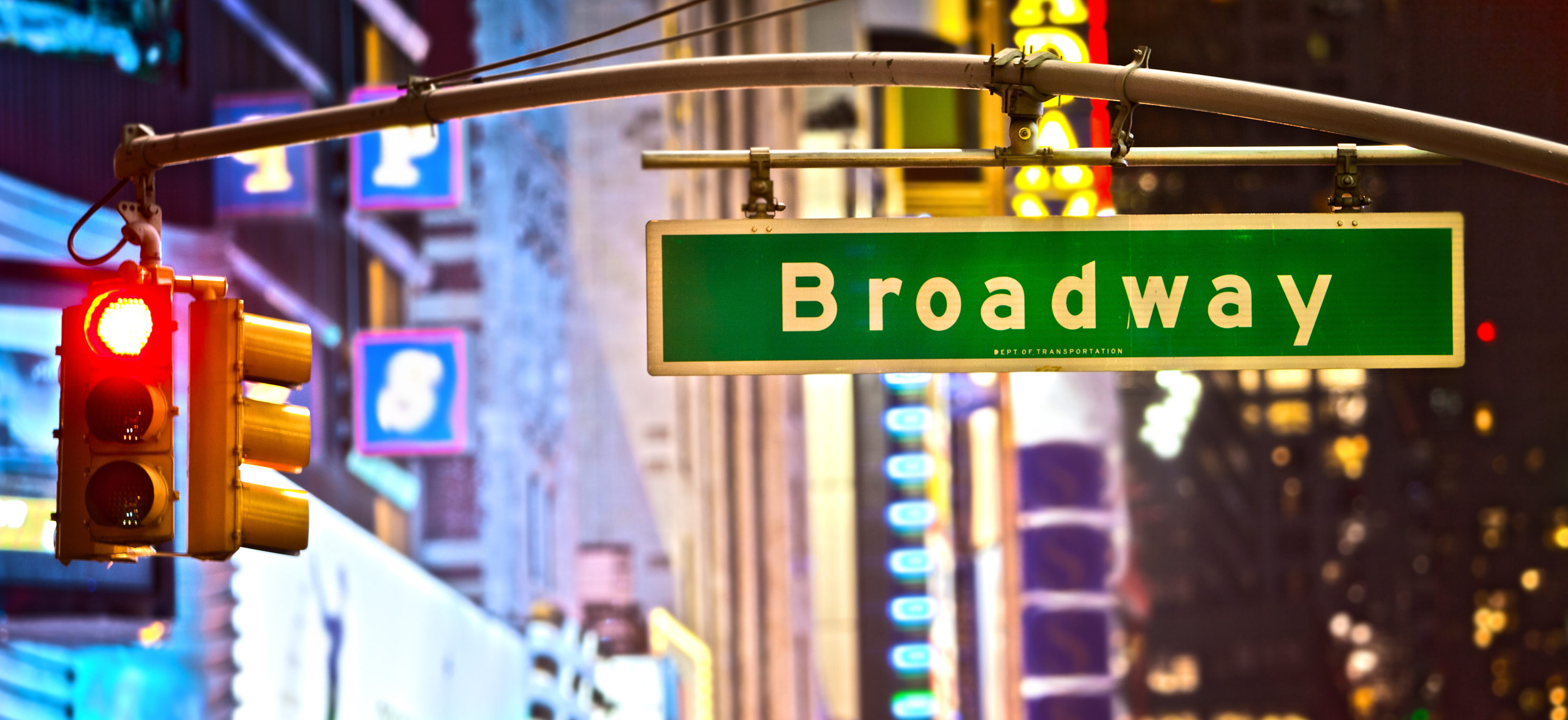 Broadway sign and red stop light in New York City at night. (Shutterstock/Stuart Monk)