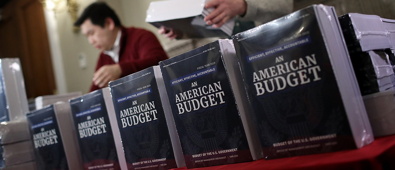 Staff members display recently released printed copies of U.S. President Donald Trump's fiscal year 2019 budget at the House Budget Committee on Capitol Hill February 12, 2018 in Washington, DC. The budget is expected to contain funding requests for the building of a wall on the southern border of the U.S., infrastructure projects, and increased military funding.  (Photo by Win McNamee/Getty Images)
