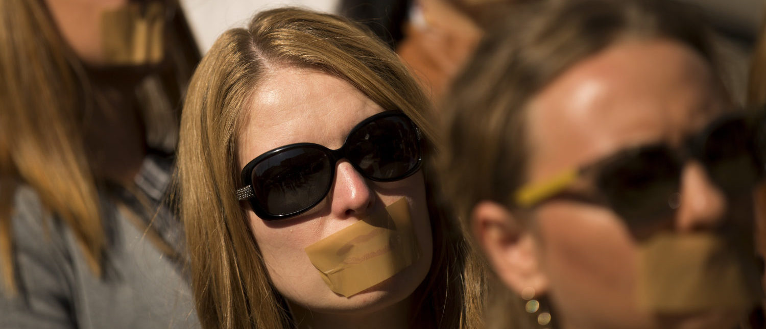 Journalists protest with taped mouths against censorship. [Shutterstock - Veselin Borishev]