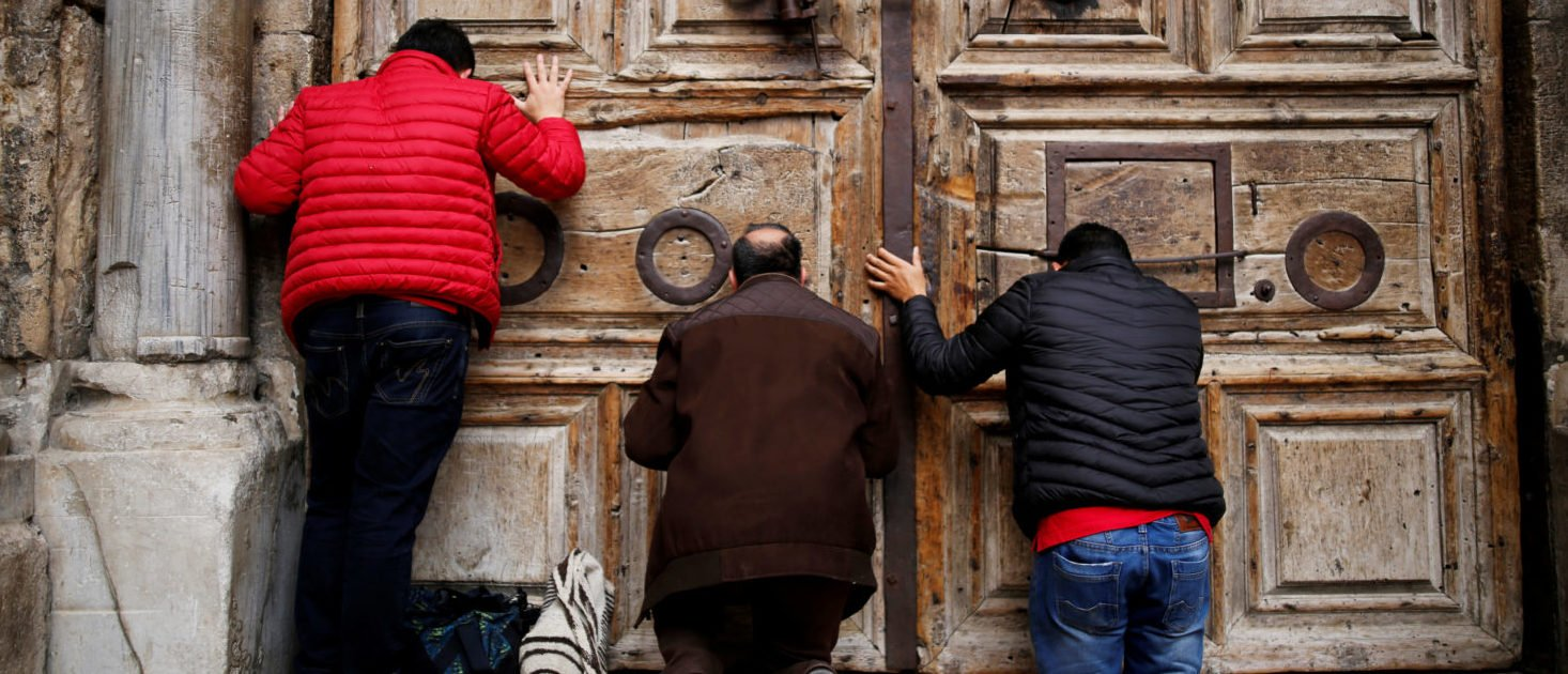 Worshippers kneel and pray in front of the closed doors of the Church of the Holy Sepulchre in Jerusalem's Old City, February 25, 2018. REUTERS/Amir Cohen
