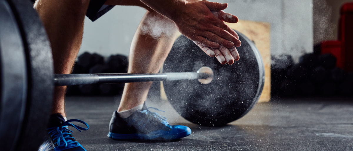 Closeup of weightlifter clapping hands before barbell workout at the gym. (Shutterstock/baranq)