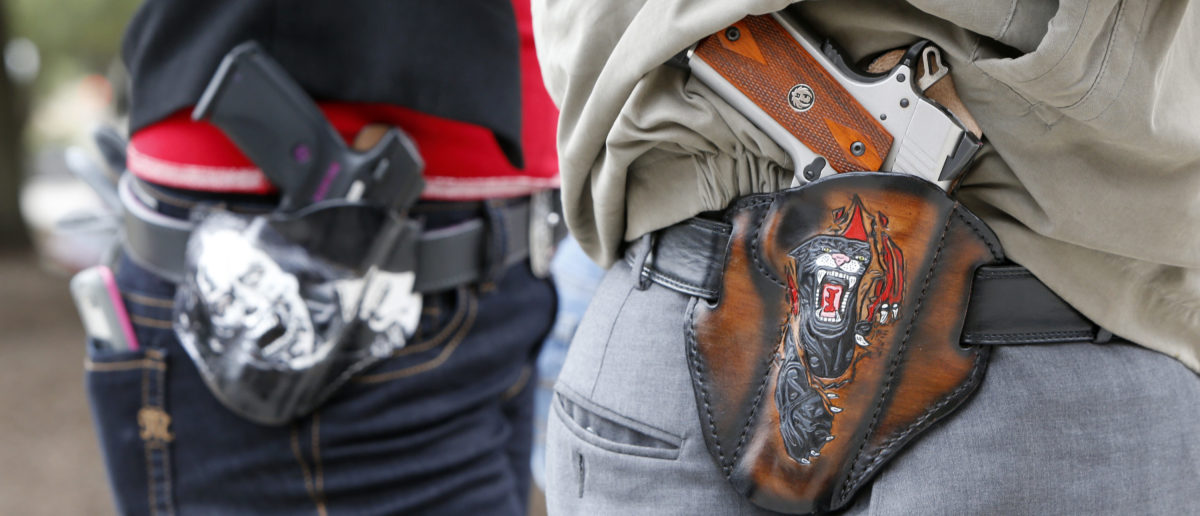 Art and Diana Ramirez of Austin with their pistols in custom-made holsters during and open carry rally at the Texas State Capitol on January 1, 2016 in Austin, Texas. (Photo by Erich Schlegel/Getty Images)