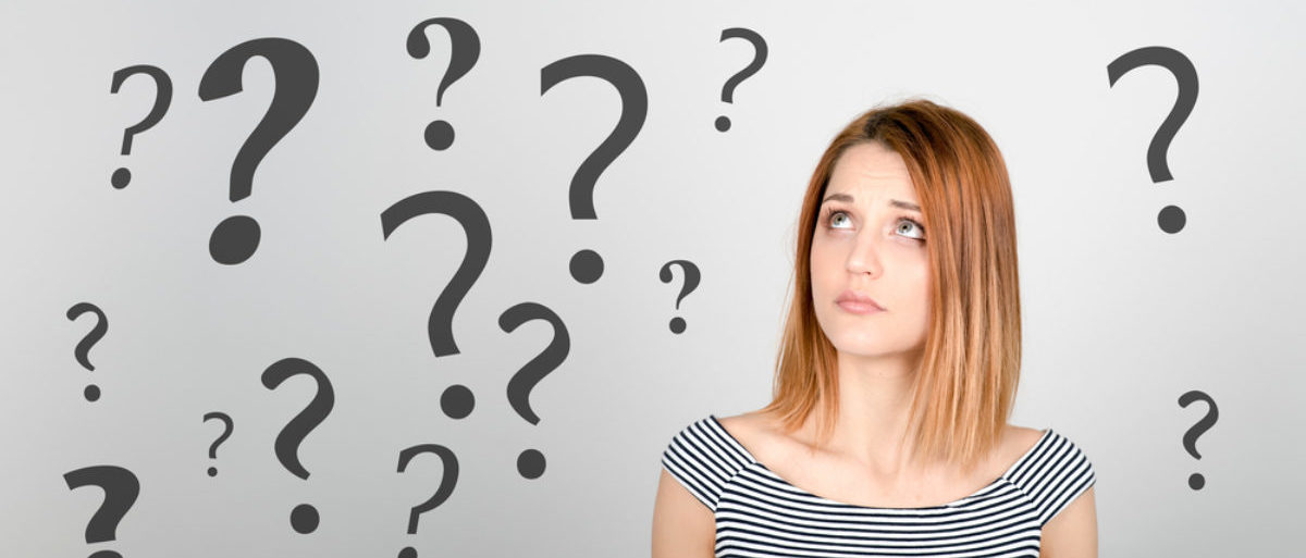 A woman is confused why there are question marks suspended in the air around her. (Shutterstock/Peppinuzzo)