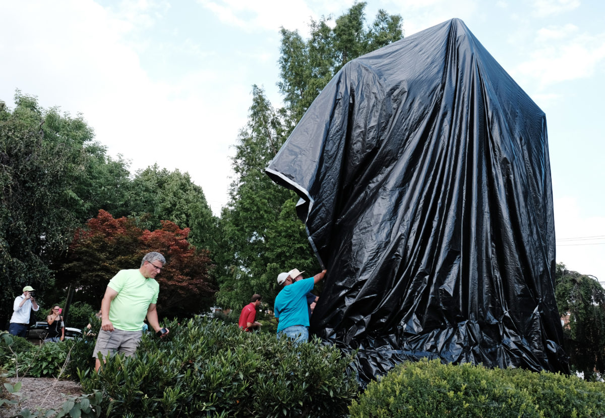 Workers replace the black tarp with which the City of Charlottesville covered the statue of Confederate General Robert E. Lee after John Miska (not shown) attempted to remove the covering in Charlottesville, Virginia, U.S., August 23, 2017. REUTERS/Justin Ide