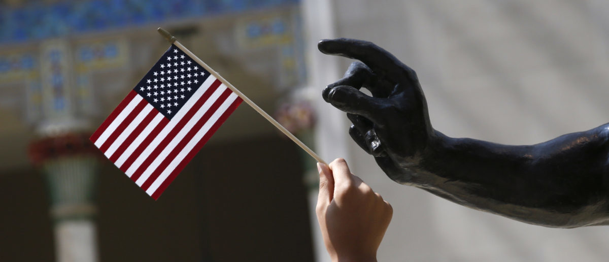 A girl holds a U.S. flag next to a sculpture after a naturalization ceremony at The Metropolitan Museum of Art in New York July 22, 2014. Seventy-five people from 42 countries became American citizens at an event held by U.S. Citizenship and Immigration Services (USCIS) at the Museum. REUTERS/Shannon Stapleton