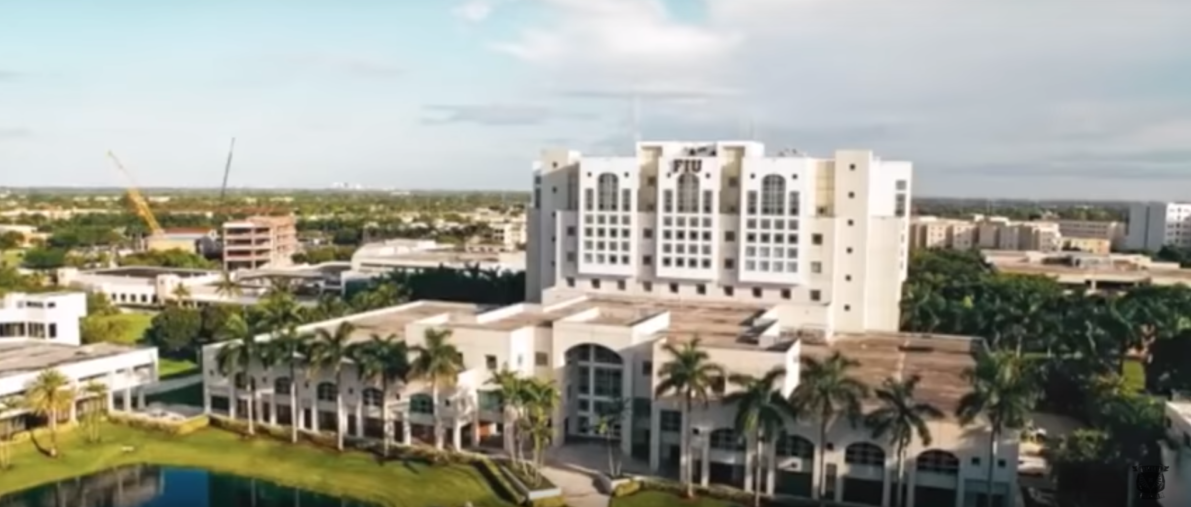 Palm trees surround a building at Florida International University. (Photo Credit: YouTube/Division 1)