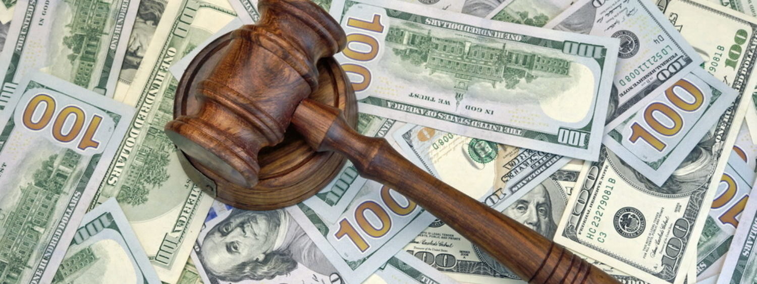 A judge's gavel over a lot of money, signifying a big monetary penalty.[Shutterstock - AVN Photo Lab]