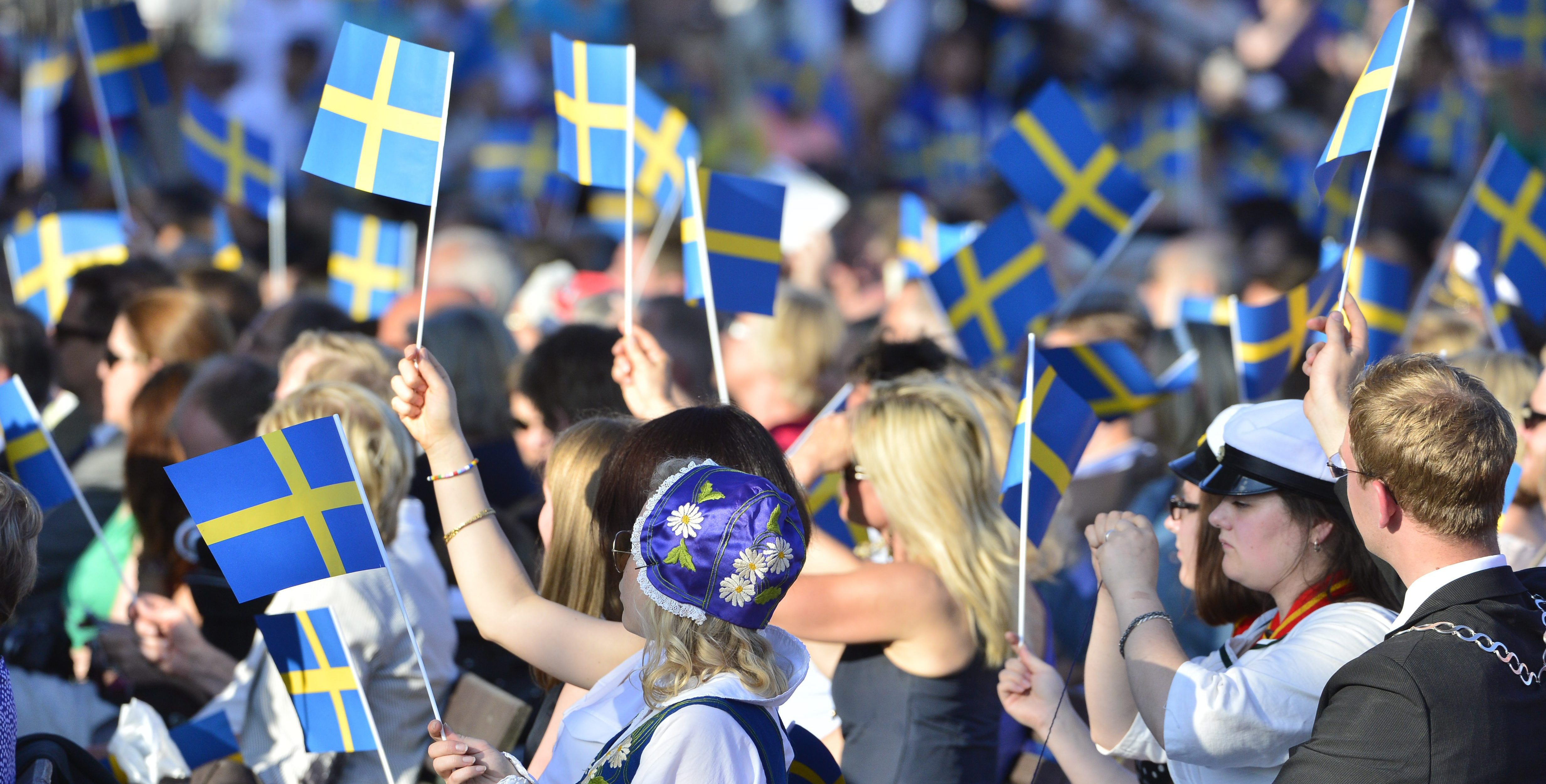People wave Swedish flags during the traditional National Day celebrations with the royal family at Skansen in Stockholm, Sweden, on June 6, 2013. AFP PHOTO / SCANPIX SWEDEN / HENRIK MONTGOMERY (Photo credit should read HENRIK MONTGOMERY/AFP/Getty Images)